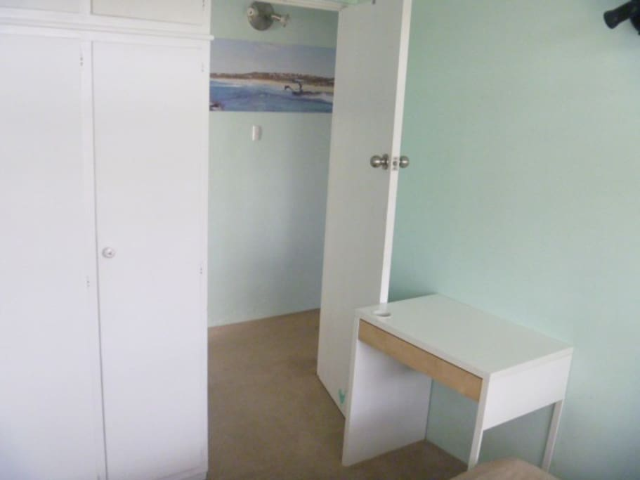 Wooden built in robe and desk in available room. Room next to bathroom.