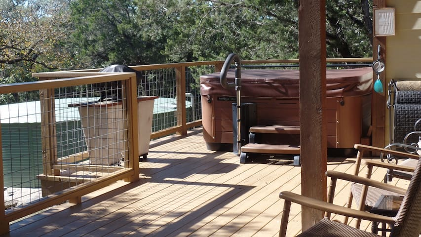 Spectacular private front deck with premium hot tub, grill and rocking chairs.