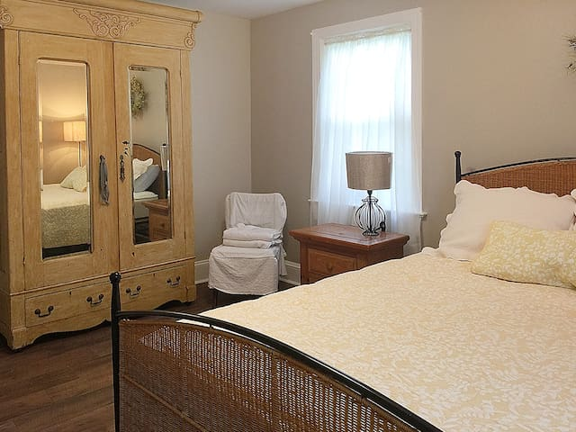 Queen bed and mirrored armoire.