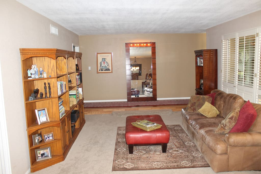 Living room with piano, stereo, comfortable space and access to front yard, dining room and family room.
