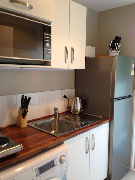 Kitchen with front loading washing machine, fridge/freezer