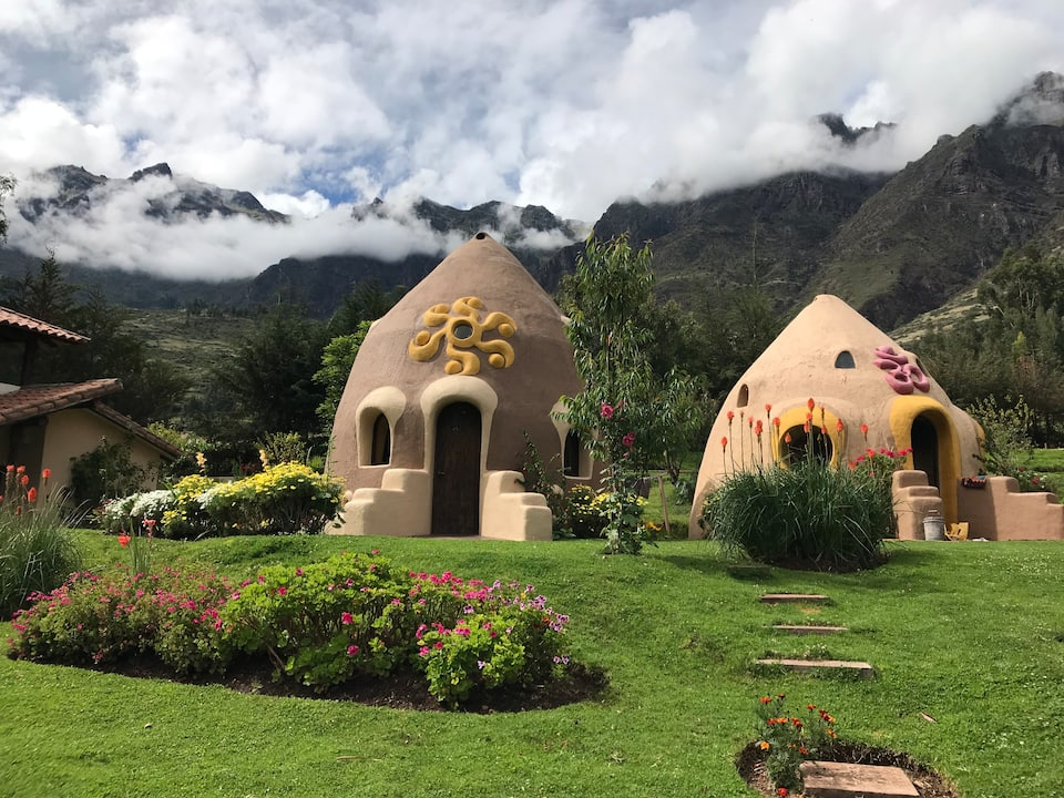 Dome House in Sacred Valley, dried earth huts with decorative yellow and pink moldings and lush green landscape.