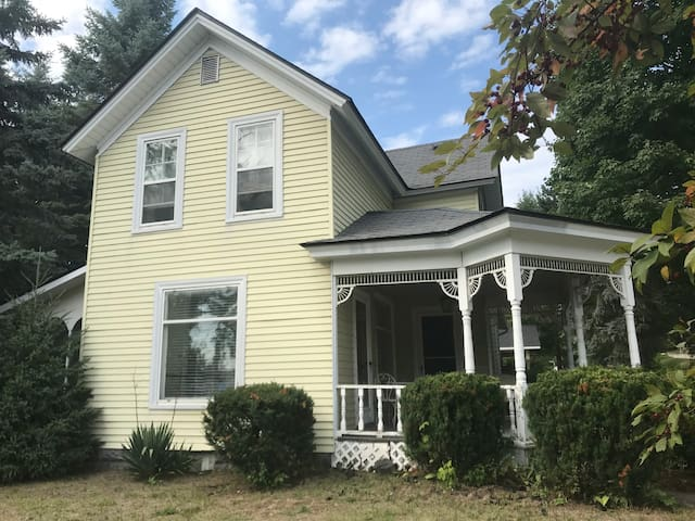 Landmark home in East Jordan offers 4 available bedrooms, two living areas, large kitchen, 1 bathroom + bonus shower, washer/dryer, 4 porches and covered parking.
