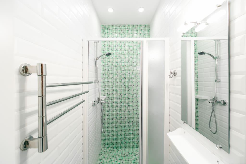 Общий вид ванной комнаты. Душевая кабина, удобные выдвижные ящики, банные принадлежности.