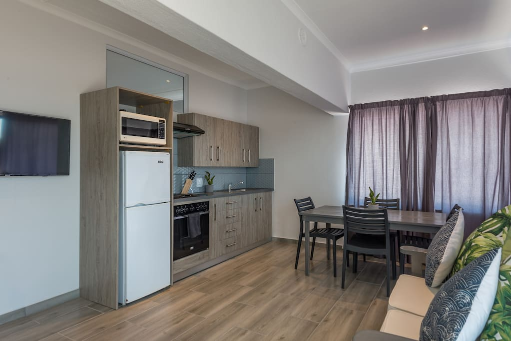 Kitchen with oven, hob and fridge and microwave