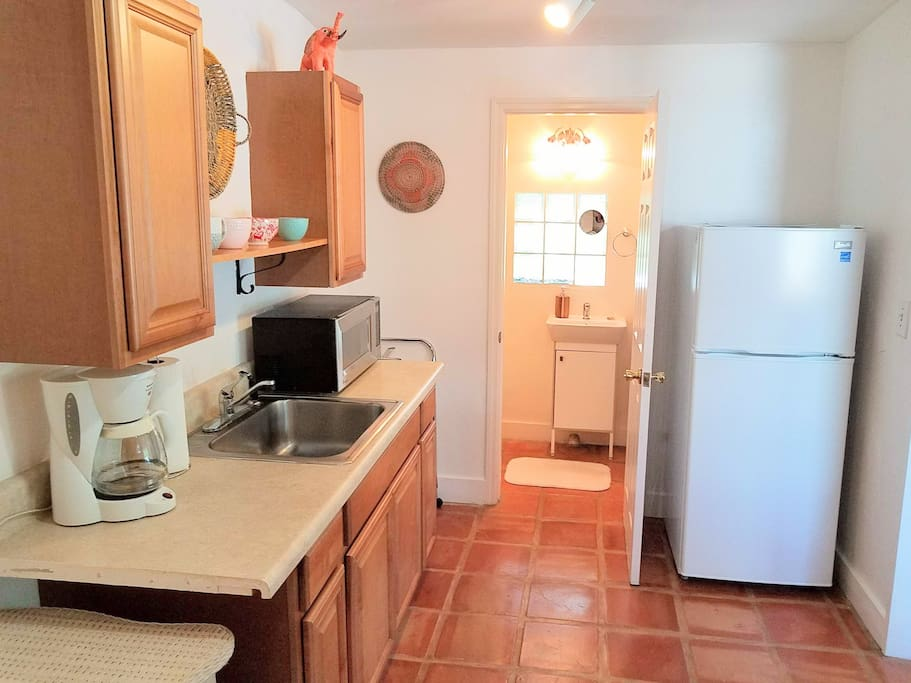 Kitchen area has a stainless steel sink, microwave, full fridge and freezer, toaster oven and cooktop.