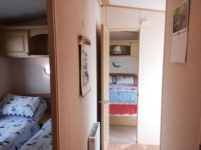 Hallway showing bedrooms and second front door entry.