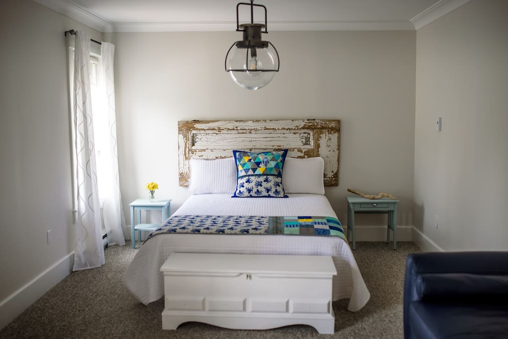 Comfy queen bed with custom Pillows and Bed Runner by local textile artist Valerie Levy.