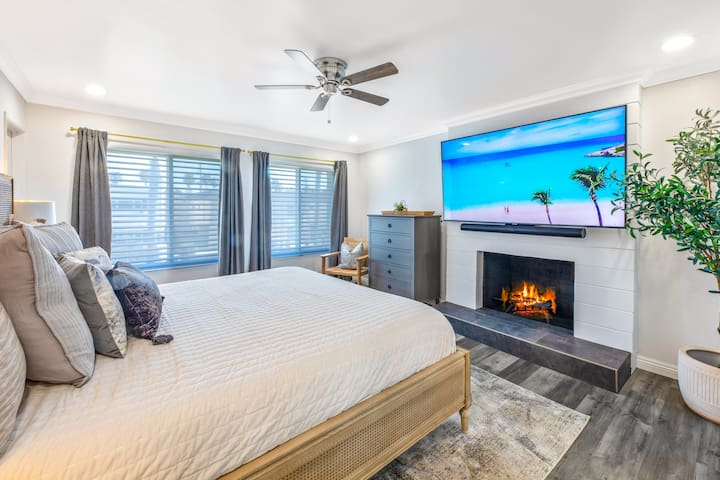 """Master bedroom with king size Tempur-Pedic bed, gas fire place and 75"""" 4K TV."""