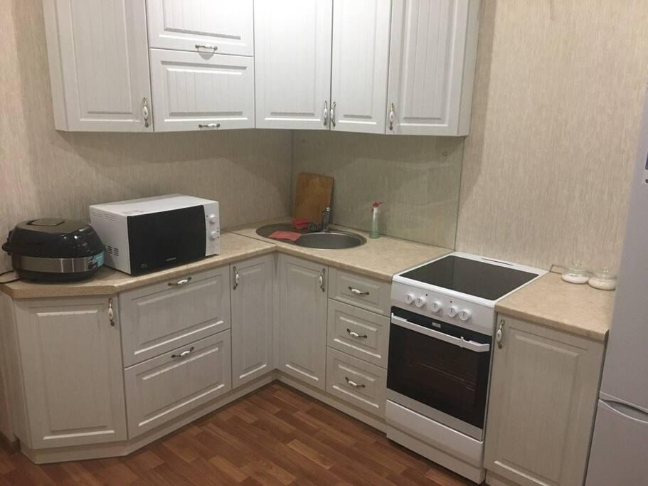 На кухне есть гарнитур,  большой холодильник, плита, духовка, мультиварка, микроволновка, так же вся необходимая посуда