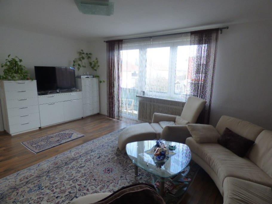 Wohnzimmer mit Balkon und TV