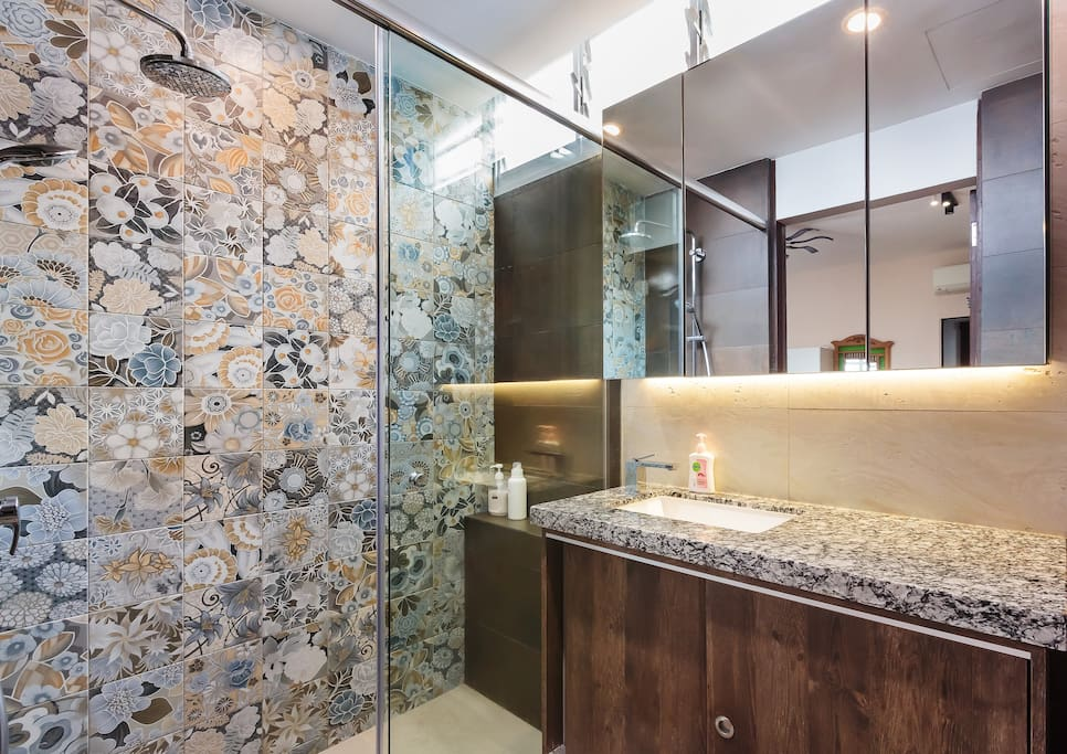 Spacious rainshower (top left) shower area separated and separate granite countertop area, which are separated by glass doors.