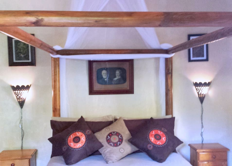 Four poster double bed with mosquito net.