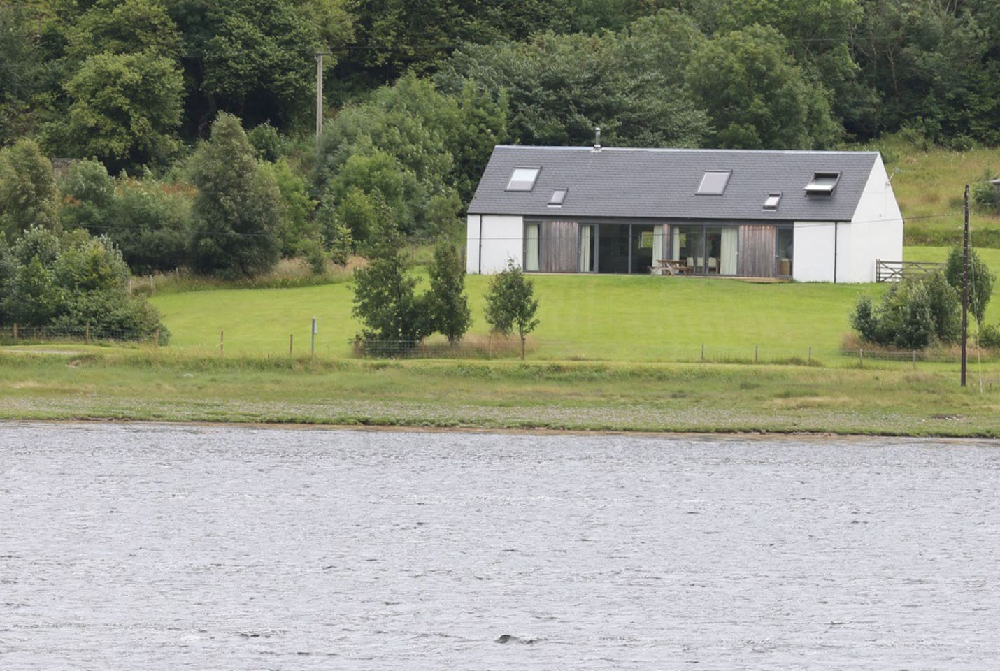 View of the lodge with large grassy enclosed front garden, and open views down to the shore and Loch
