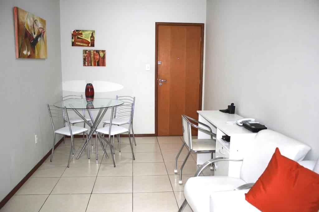 Sala de estar espaçosa com televisão, mesa e escrivaninha para trabalho ou estudo.