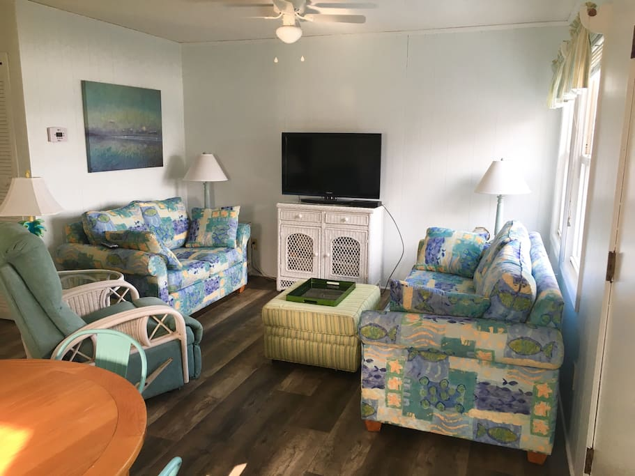 Comfortably furnished living room with flat screen TV.