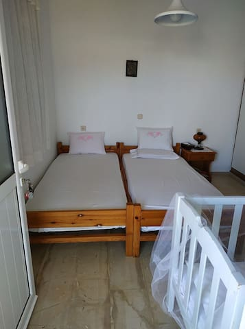 This is the one of the two bedrooms. There are two single beds and a baby's bed. There is also a large mirror in the room and a quite big wardrobe.