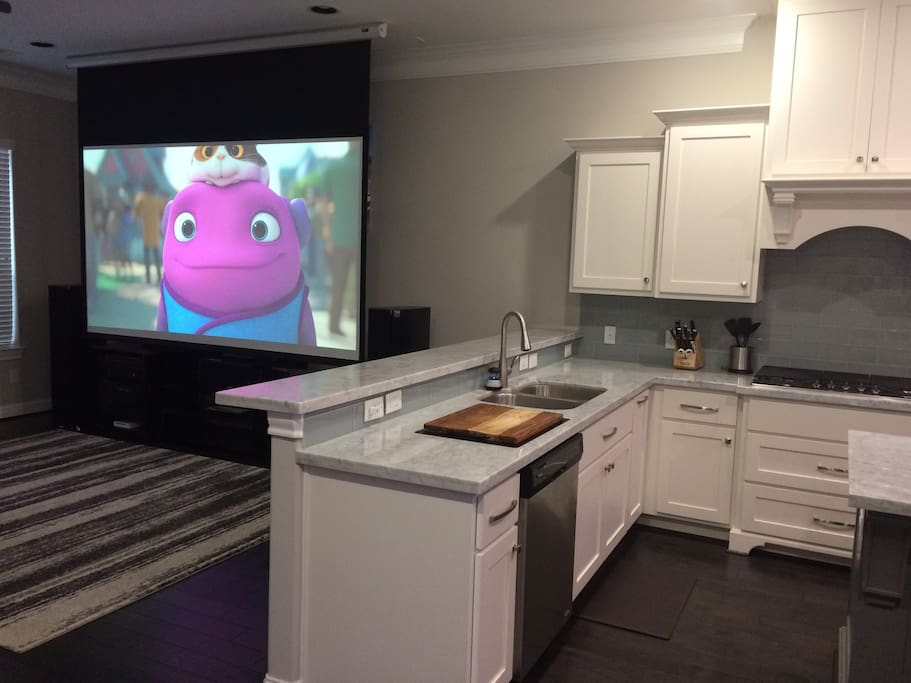 """View into living room with 120"""" drop down projection screen."""