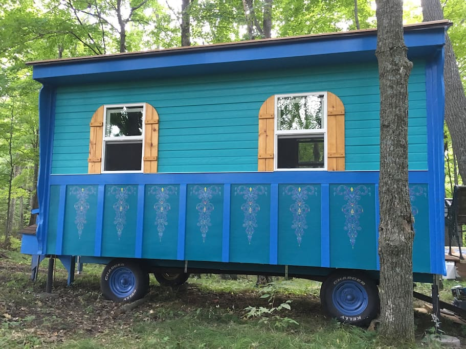 """The Gypsy wagon, also known as a """"Vardo"""", is    8' x 16'. Custom made shutters and hand stenciling on the side."""