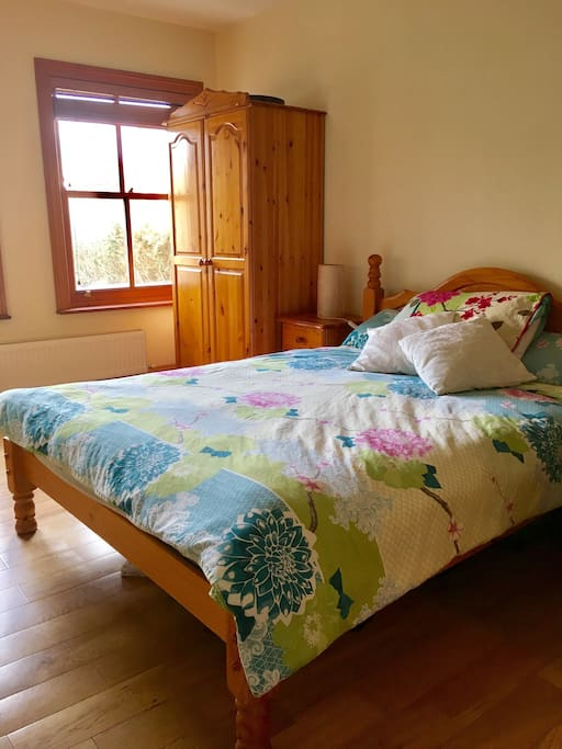 Comfy double bed in a spacious downstairs room, views of surrounding mountains out the window.