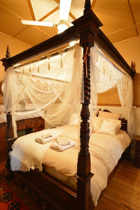 Master bedroom, hand carved four poster bed.  Sink into this cozy queen bed and enjoy the atmosphere. Ceiling fan.