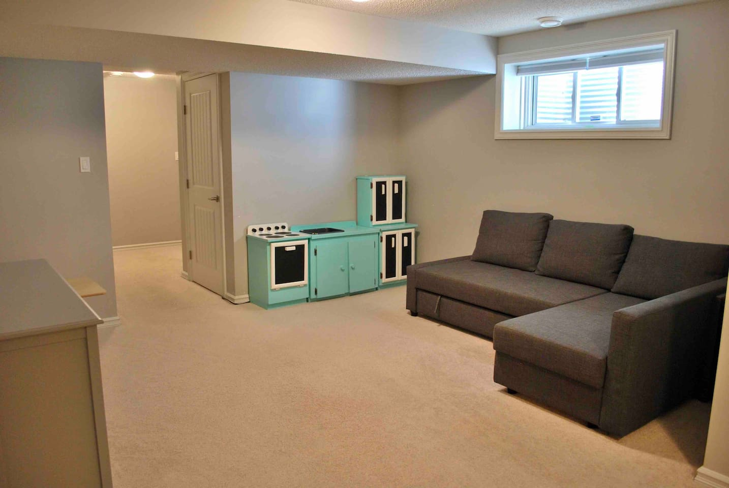 Living room with double sofa bed and children's play kitchen