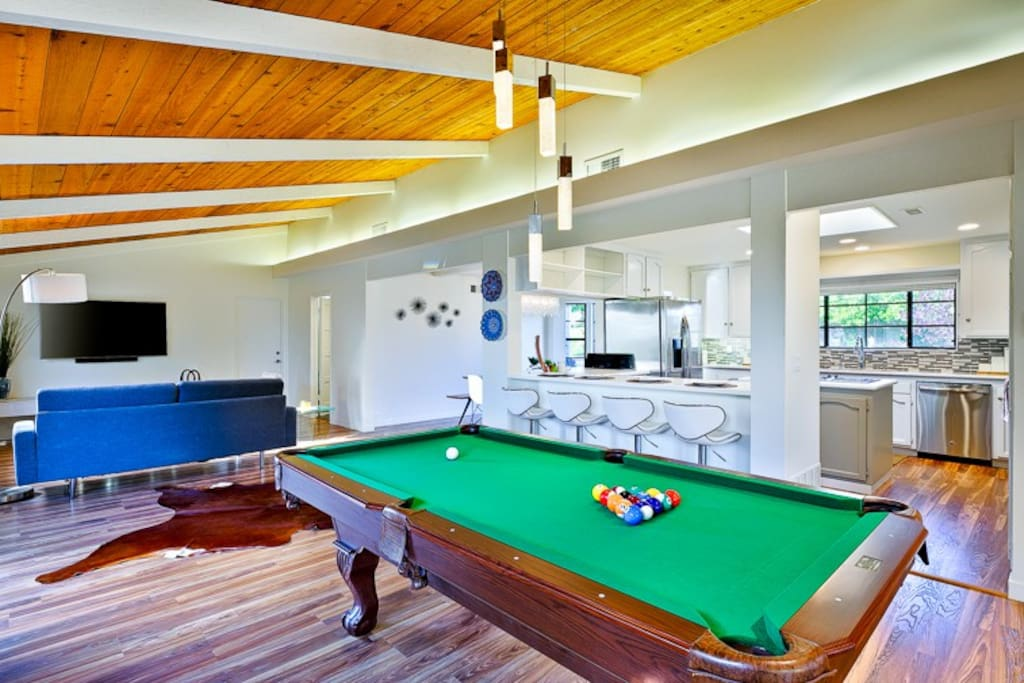 Game room with pool table and flat screen TV.
