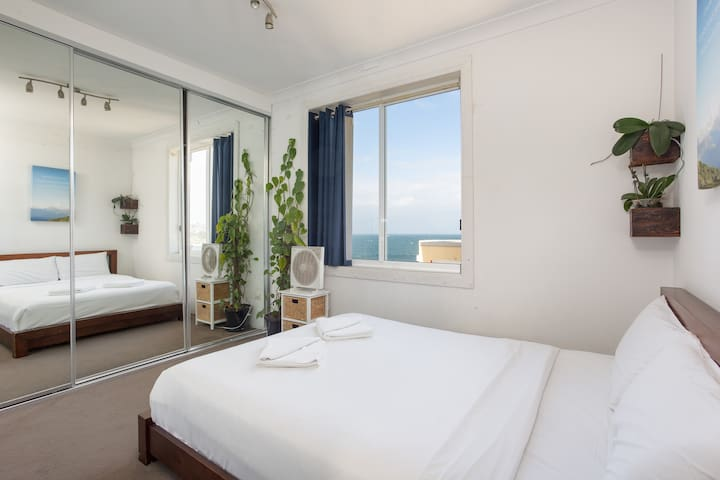 The light-filled master bedroom is fitted with a premium queen-sized bed and topped with crisp white linens. There is a built-in wardrobe providing ample storage space for your belongings.