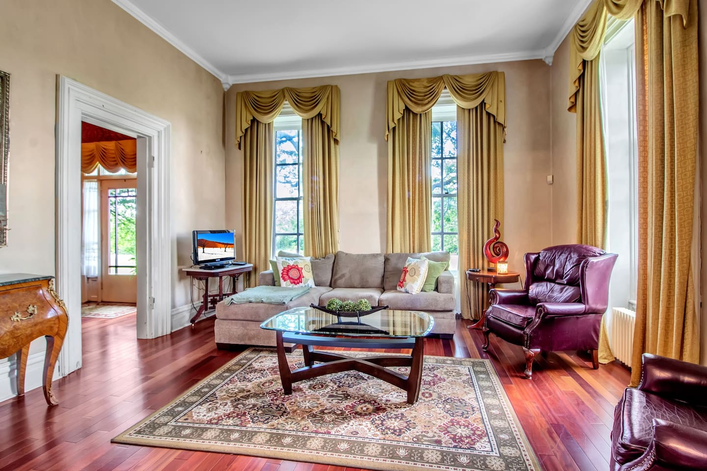 The Living Room of the Vineyard Manor House is Shabby Chic with 14' ceilings and swagged drapes on the plantation style windows.