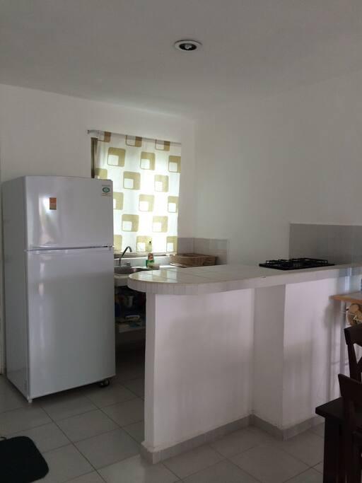 Cocina con refrigerador, estufa y horno de microondas.