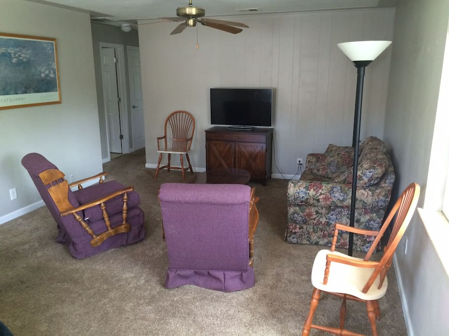 The living room contains a love seat, comfortable couches and a Smart TV