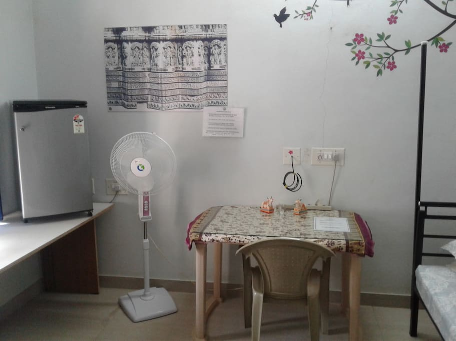 Another view of work table , pedestal fan , fridge .