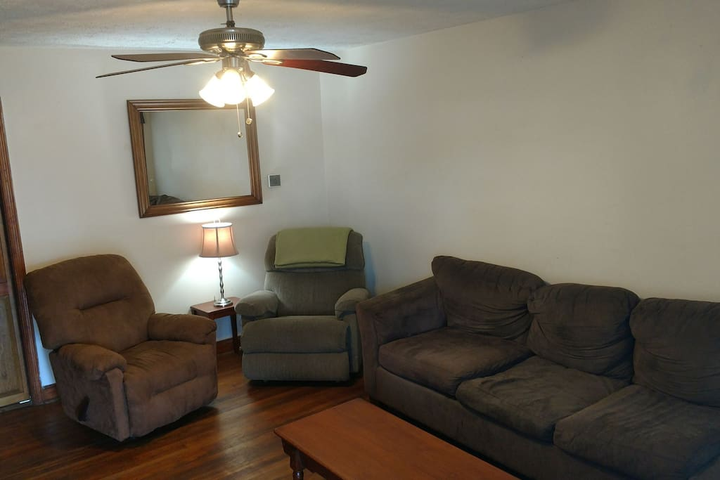 Living room with two reclining chairs and an L shaped couch.
