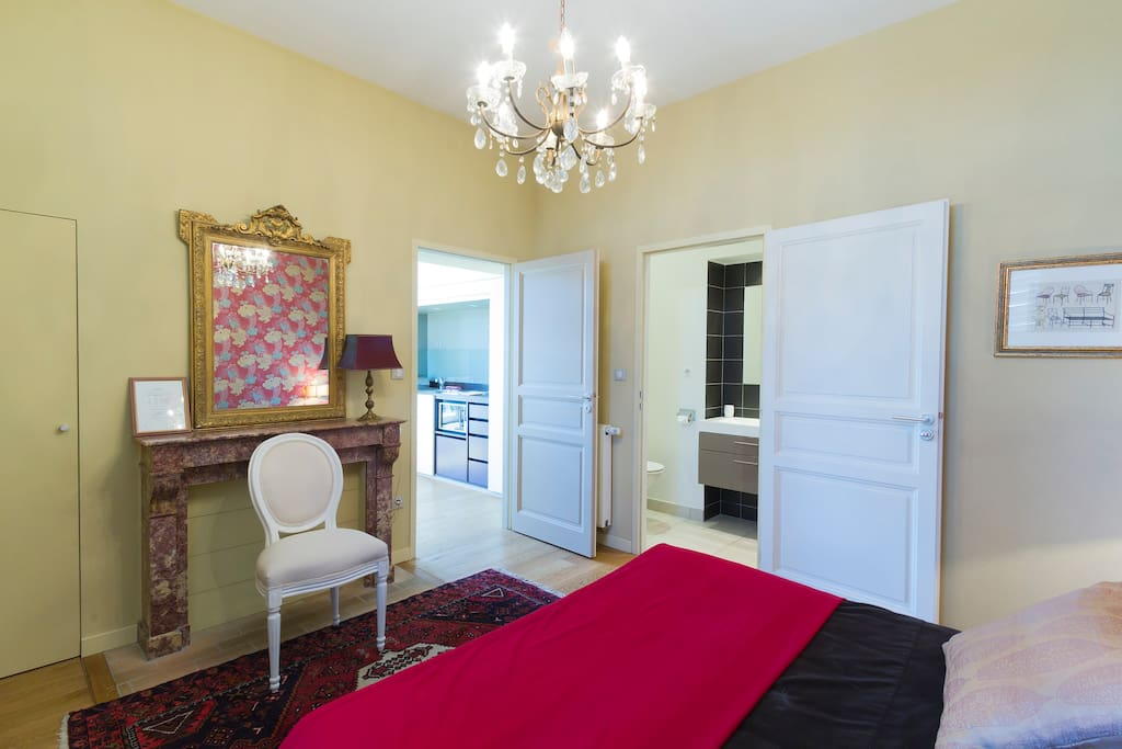 La Jacques Brel bedroom with access to kitchen area (left) and access to bathroom (right)