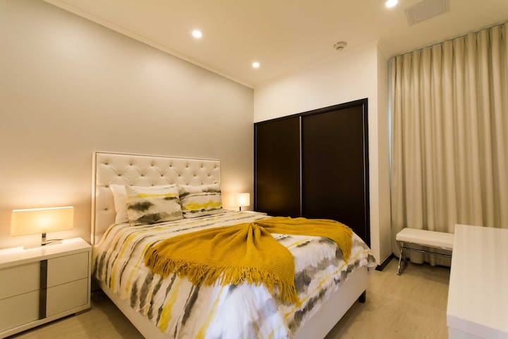 The third bedroom with a queen-size bed and built-in closet