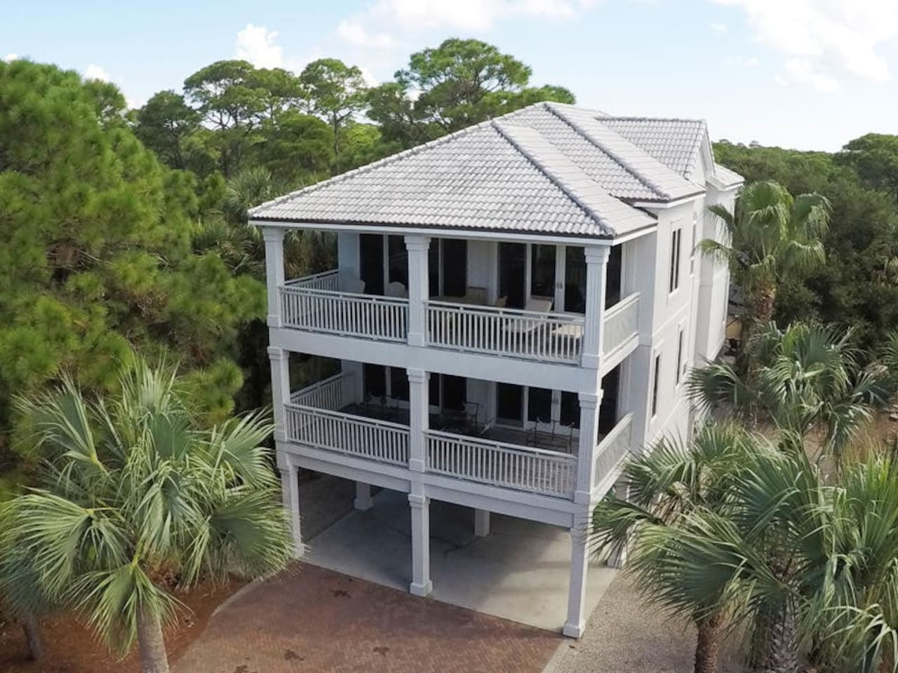 SUNSATION IS YOUR PREMIER DESTINATION! This stunning home is tucked back on a beautifully landscaped lot within the exclusive gated community called Schooner Landing.This lovely home is just steps away from the marvelous Bob Sikes Cut with gorgeous views of the gulf and little St. George Island! The perfect getaway for fishing, shelling or watching the dolphins play in the surf! This dazzling home has 5 bedrooms with their own private bathrooms! A large ground level bedroom has been prepared as the kid's bunk room, set up with 2 single bunks, TV and private bathroom. The 1st level is the main bedroom level, with 2 guests suites; one with a king bed and the other guest suite with 2 twin beds, a laundry room and a grand Master bedroom suite, with a Jacuzzi tub, morning kitchen, large screen TV and its own private covered porch. Up the stairs is the main living area with a generously appointed living room, new furniture and decor, a large TV, and opens to another large covered porch with some of the best views around.The open concept kitchen makes for ease of conversation and entertaining, with plenty of cabinet and counter space and even a large island with 3 bar stools. The dining room can easily accommodate seating for 8, so offering plenty of space for large family dinners. Just off the dining room is the half bath and another Master bedroom with a king bed and its own private bathroom. All bedrooms have sliding glass doors leading to expansive covered decks, with either beautiful views of the lush landscape, private screened enclosed pool and tennis courts or stunning views of the gulf, Bob Sikes Cut and our famous SGI sunsets! Don't miss your opportunity to experience the best St. George Island life for your family's vacation!