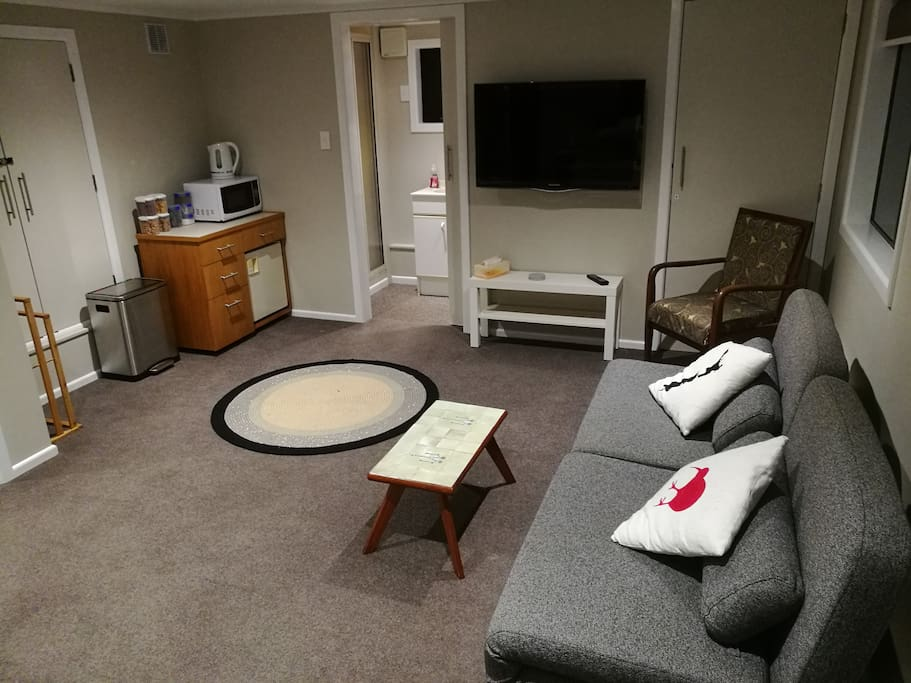"""A view of the lounge side of the Suite. A wall mounted 40"""" TV and comfy sofa. Ensuite visible at the back."""