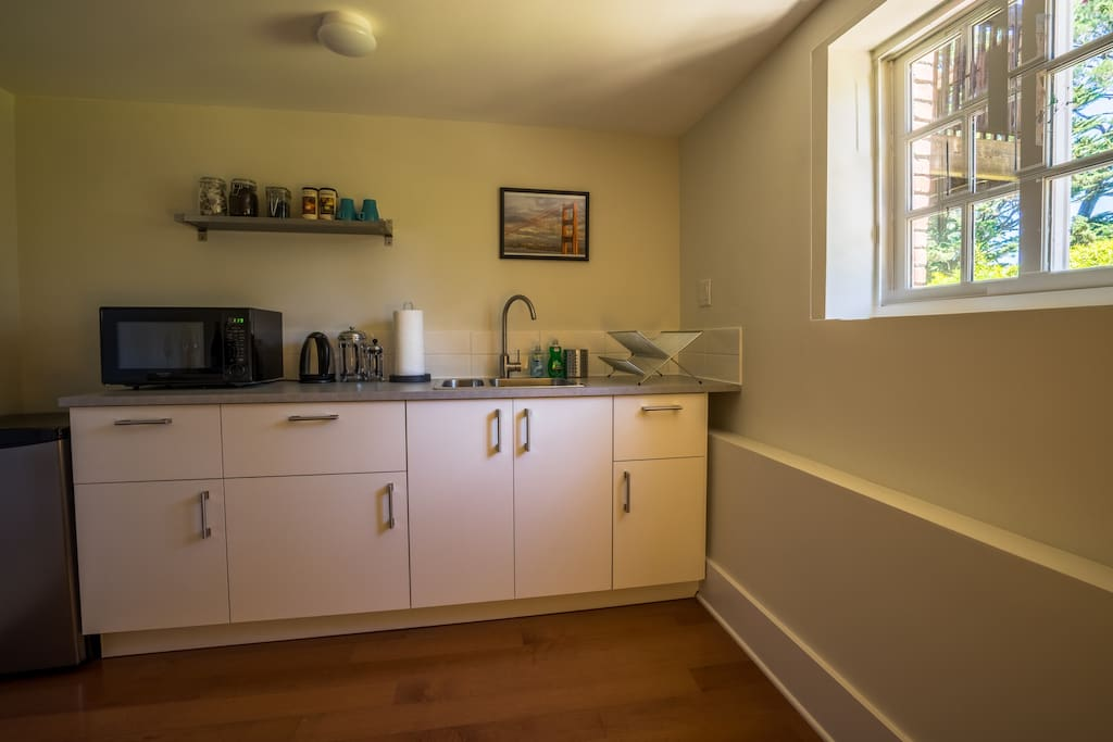 Kitchenette with fridge, microwave, coffee making, crockery and silverware