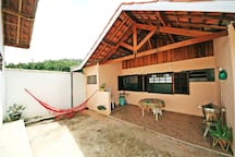 Área de lazer em frente da casa com rede, churrasqueira, taque, mesa, cadeiras, hortinha de temperos.