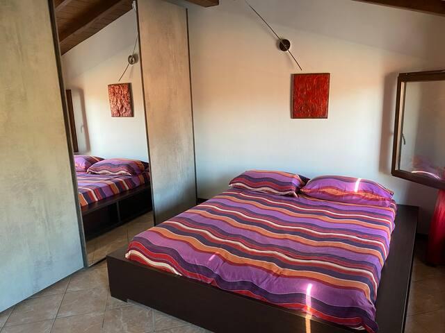 La camera da letto è composta da un grande armadio per i vestiti, da un letto matrimoniale predisposto con un materasso di ottima qualità   bedroom consists of a large wardrobe for your clothes, a double bed prepared with a high quality mattress