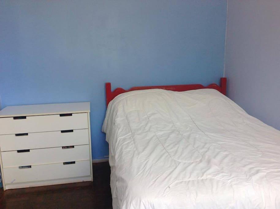 quarto com cômoda, mesa, ventilador e ar condicionado