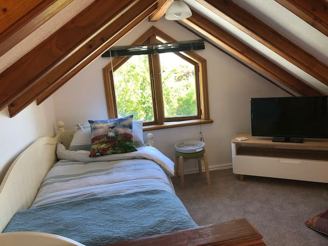 Loft room showing king day bed with actual guest bedding