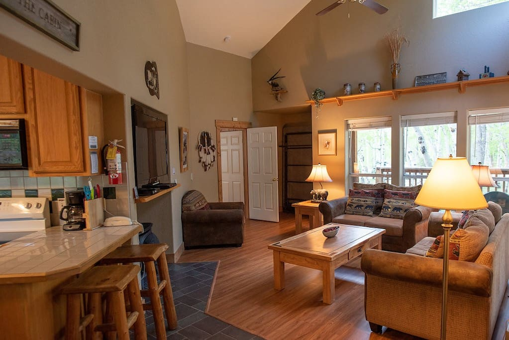 Relax in the spacious living room with vaulted ceilings, large windows, gas fireplace and TV.