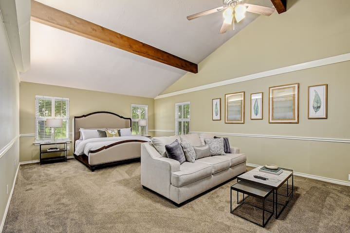 The grand master suite features a king size linen upholstered bed accompanied with mango wood and iron nightstands adding a traditional touch.