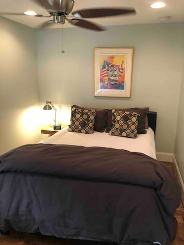 Queen size bed with coverlet and duvet.
