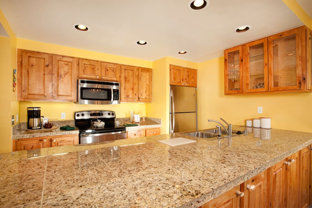 The fully-equipped kitchen features stainless steel appliances