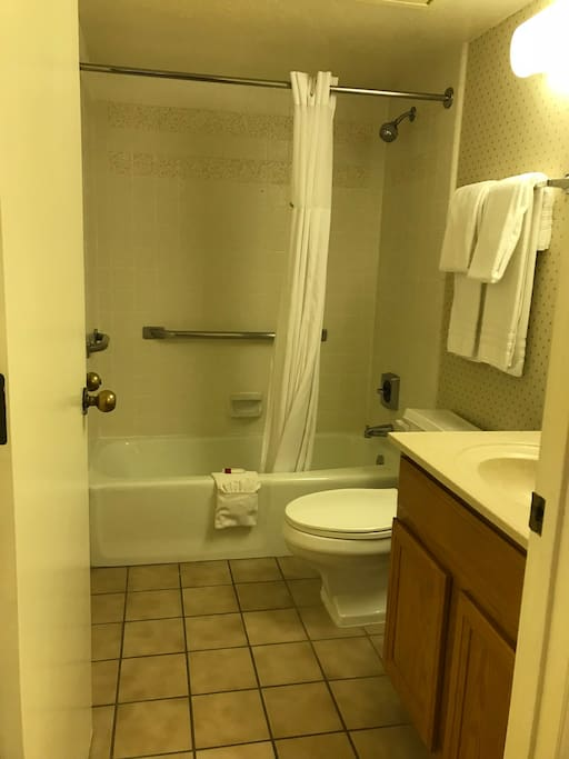 Bathroom has two vanities, shower, tub, linens, and toiletries