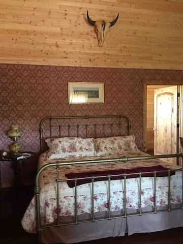 The king size bed is downstairs in the main room, right by the bathroom.