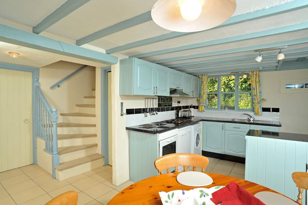 Kitchen and dining room, with dishwasher, washing machine, oven hob and microwave leading onto bathroom and sweeping staircase