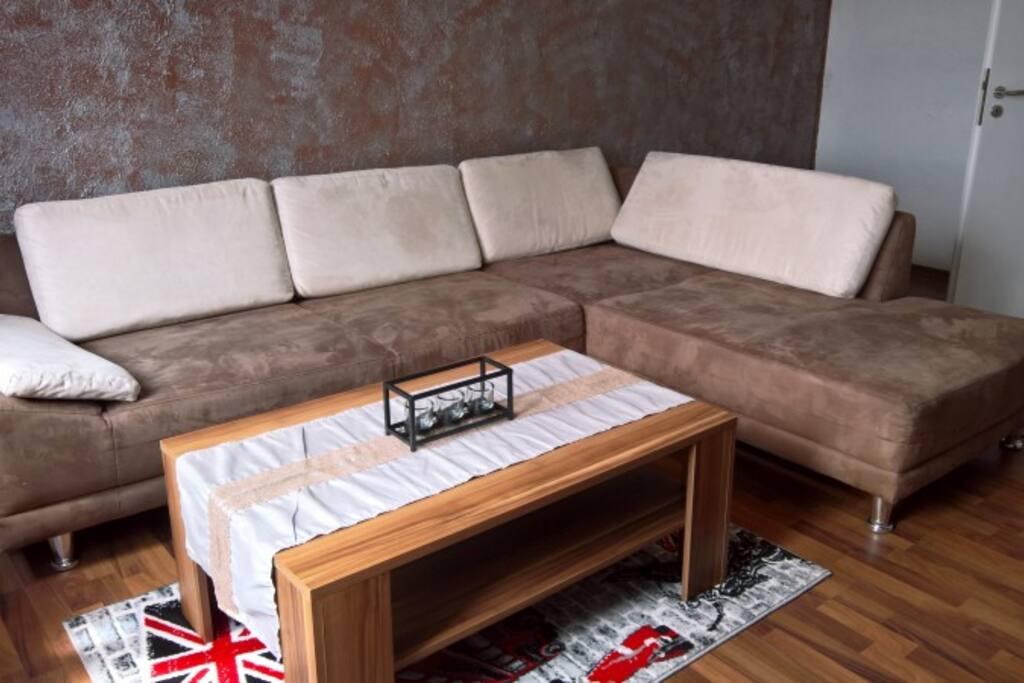 Wohnzimmer mit grosser Eckcouch, TV-Wand mit Flatscreen, Kratzbaum und  Hundekorb